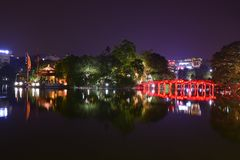 Night view with water reflection of The Huc Bridge in bright red with Ngoc Son Temple, Hanoi, Vietnam.
