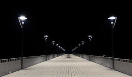 Night view of a wooden pier and lamp posts Stock Image