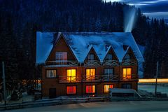 Night view of wooden snowy house. With warm lights in windows Royalty Free Stock Images
