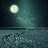 Night vintage Landscape with Tire Trace. On snow, stars and full moon in sky. Film filter Stock Photo