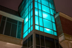 Night vision. Night shot of glass office building window glass lit with blue purple light room for type above building Royalty Free Stock Images