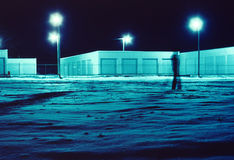 Night Walk. Blurred figure walks in snow at night with illuminated storage buildings in background Royalty Free Stock Photos