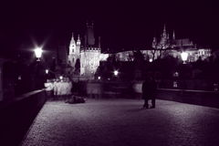 Night walks. Photo of a beggar and pedestrians on st charles bridge in prague in black and white stock images