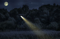 Night on the watchtower. On the watchtower spotlight shines Stock Image