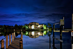 Night on the water. Beautiful photo illustration of nighttime on a dock looking across water to florida mansion reflected in the bay under a cloud covered sky Royalty Free Stock Image