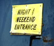 Night and Weekend Entrance. An old yellow sign on a blue steel door Stock Photos