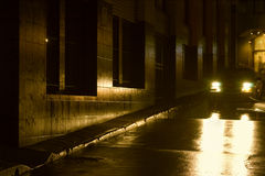 Night - Wet Night in the City. Car headlights reflecting on wet city street Royalty Free Stock Image