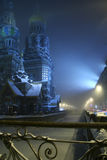 Romantic foggy night winter city with a cathedral and a frozen canal Stock Images