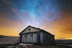 Night winter landscape. Abandoned wooden house in the background of the night starry sky in bright colors and sunset. Night winter landscape. Abandoned wooden Royalty Free Stock Image