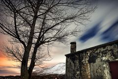 Night winter landscape. Old abandoned house near big dry tree, sadness and loneliness concept Royalty Free Stock Images