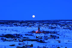 Night in winter town. The shine full moon over the town Stock Images