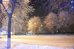 Night winter town Avenue. All in the snow street trees houses lamp posts wires. The light in the Windows of houses Royalty Free Stock Image