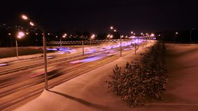 Night Winter traffic. Timelapse: cars move along the highway, leaving behind a trail of light stock video