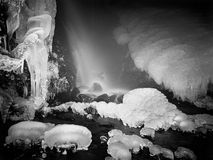 Night winter view to frozen cascade of waterfall, icy twigs and icy boulders in frozen foam of rapid stream. Reflections of light Stock Images
