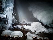 Night winter view to frozen stream below  waterfall, icicles and icy boulders in the stream. Royalty Free Stock Photo