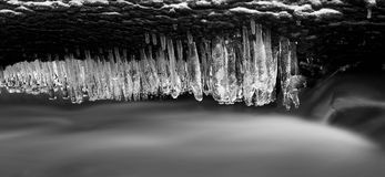 Night winter view to icicles on twigs and icy boulders above rapid stream. Reflections of head lamp in icicles. Black and white. Royalty Free Stock Image