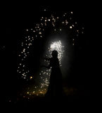 Night wizard silhoutte. Fairy girl silhoutte holding a stick with which she is spreading the magic and sparks around her stock images