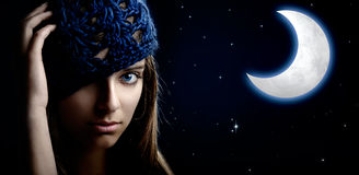 Night Woman. Portrait of a beautiful and young woman at night with a artifical moon on the background Stock Images