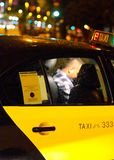 Yellow Taxi. Using a blak and yellow traditional barcelonese cab during a rainy night with city lights in background Stock Images