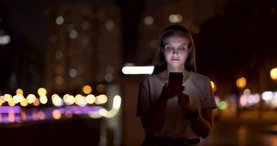 At night, a young girl holds a smartphone in her hands and looks at the screen. At night, a young girl sits on the grass in a big city and looks into the stock video