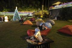 Nightby la hoguera en un jardín del hotel con los beanbags grandes Fotografía de archivo