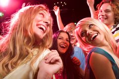 In the nightclub. Several smiling dancers having fun during disco Stock Photography