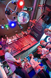 Nightclub. Crowd of people around a guitar player and saxophonist in a trendy nightclub Royalty Free Stock Photo