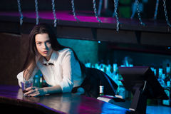 Nightclub bar bartender. Beautiful sensual brunette bartender girl in white shirt and black bow tie working at nightclub bar, offering glass with drink Royalty Free Stock Photography