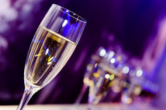 Nightclub champagne glass. Luxury party champagne glass in nightclub neon lilac, blue and purple lights. Blurry closeup Royalty Free Stock Photos