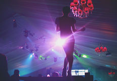 Nightclub dancer. Silhouette of young female dancer who is entertaining the partying audience in a nightclub Royalty Free Stock Image