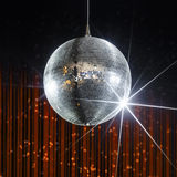 Nightclub disco ball. Party disco ball with stars in nightclub with striped orange and black walls lit by spotlight, nightlife entertainment industry Stock Image