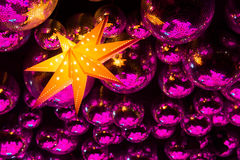 Nightclub disco balls and star. Silver disco balls in party neon pink and red lights and orange star lamp in nightclub Stock Photos