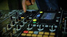 Nightclub DJ adjusting controls, twisting toggle on professional soundboard. Stock footage stock video footage