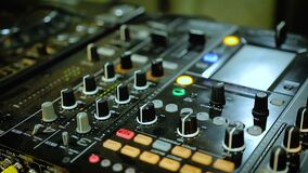 Nightclub DJ playing mix on soundboard, console with flashing lights and buttons. Stock footage stock footage