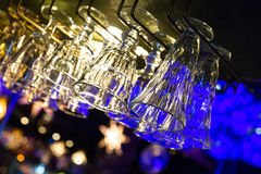Nightclub glasses. Nightclub faceted empty glasses lit by festive bar lights Stock Photography
