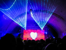 Nightclub Lasers, Crowd, Love Heart. A giant heart illuminates a TV screen while lasers give a show above the crowd Stock Image