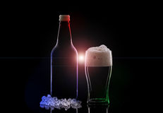 Nightclub. A Pint of Dark Beer and a Beer Bottle with Colourful Lights and Lens Flare royalty free stock photo