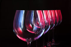 Nightclub wine glasses. Wine glasses lit by red, blue, lilac nightclub party lights on black background Stock Photo