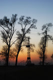 Nightfall. Trees drilling rig oilfield Stock Image