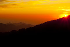 Nightfall in the mountains of Corsica, France. Beautiful golden, red and orange sunset. Nightfall in the mountains of Corsica, France. The sun slowly disappears Stock Images