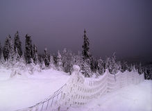 Nightfall, Snowy Landscape. Dark gray sky over a winter mountain landscape with frosted trees and a snow covered fence Royalty Free Stock Photos