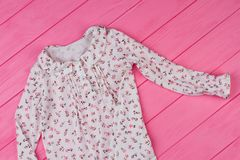 Nightgown for little lady. Pink wooden background. Ruffle collar and floral pattern. Stylish sleepwear for girls Royalty Free Stock Images