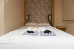 Nightgowns and towel on white bed in Japanese hotel room. Stock Photography
