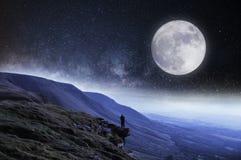 nightime编辑 在与上面月亮和星的山围拢的峭壁边缘的一个徒步旅行者 库存图片