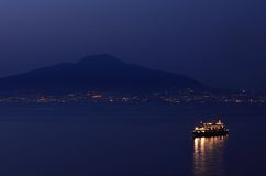 Nightime view of Vesuvius, from Sorrento, Italy. View of the volcano, Mount Vesuvius, with lights of the towns across the Bay of Naples, and a brightly lit Royalty Free Stock Photography