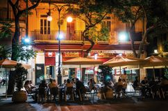 Nightlife with cafe in Valencia, Spain. Valencia, Spain - June 2, 2017: Tourists and locals rest in cafe and restaurant on narrow streets with at night Royalty Free Stock Images