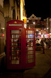 Nightlife in Chinatown, London. People enjoy the Friday nightlife next to a typical telephone booth in Chinatown in London on August 16, 2013. With a large Royalty Free Stock Photos