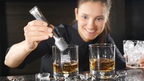 Nightlife in a club. Female barman preparing alcoholic cocktails in wineglasses putting cubes of ice in slow motion. Ice. Is falling down with splashes stock video