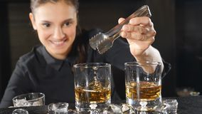 Nightlife in a club. Female barman preparing alcoholic cocktails in wineglasses putting cubes of ice in slow motion. Ice. Is falling down with splashes stock footage