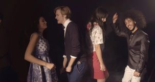 Nightlife concept, smiling young people smiling and dancing. Friends in disco club having fun stock footage